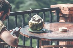 BALI INDONESIEN - MAJ 17, 2018: Man med den nya organiska kokosnöten som kopplar av på en watefallbakgrund i djungeln av Bali Royaltyfri Fotografi