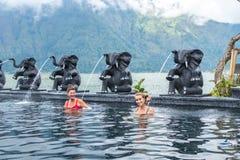 BALI INDONESIEN - MAJ 5, 2017: Två sunda höga kvinnor som simmar i natursimbassängen aktiv livsstil _ Arkivbilder