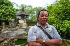 Bali Indonesien - mars 22, 2018: En Bali chaufför som ler på kameran på den Batuan templet fotografering för bildbyråer