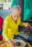 BALI INDONESIEN - MARS 08, 2017: Gammal kvinna som förbereder en indisk Sadhu deg för chapati på Manmandir ghat på bankerna Arkivfoton