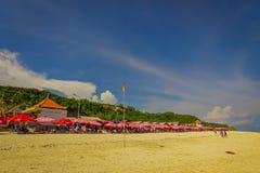 BALI INDONESIEN - MARS 11, 2017: Härlig solig dag med paraplyer i rad i stranden av den Pantai pandawaen, i Bali Arkivfoto