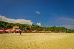 BALI INDONESIEN - MARS 11, 2017: Härlig solig dag med paraplyer i rad i stranden av den Pantai pandawaen, i Bali Arkivbilder