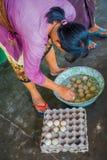 BALI INDONESIEN - MARS 08, 2017: Kvinnor som förbereder en indisk Sadhu deg för chapati på Manmandir ghat genom att använda en sk Royaltyfri Bild