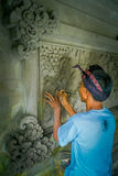 BALI INDONESIEN - MARS 08, 2017: Man som använder en stämjärn för att göra konst på en vägg av cement, i Denpasar Bali som in lok royaltyfria foton