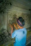 BALI INDONESIEN - MARS 08, 2017: Man som använder en stämjärn för att göra konst på en vägg av cement, i Denpasar Bali som in lok arkivbilder