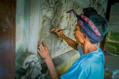 BALI INDONESIEN - MARS 08, 2017: Man som använder en stämjärn för att göra konst på en vägg av cement, i Denpasar Bali som in lok royaltyfri foto