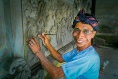 BALI INDONESIEN - MARS 08, 2017: Man som använder en stämjärn för att göra konst på en vägg av cement, i Denpasar Bali som in lok fotografering för bildbyråer