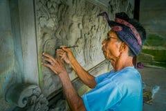 BALI INDONESIEN - MARS 08, 2017: Man som använder en stämjärn för att göra konst på en vägg av cement, i Denpasar Bali som in lok arkivbild