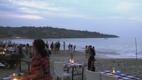 Bali Indonesien, November, 2016: Turister som kopplar av i restaurangen och på en strand Restaurang för BalineseJimbaran strand lager videofilmer