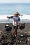 Salt produktion för traditionellt hav på den vulkaniska svart sanden, Bali Royaltyfri Fotografi