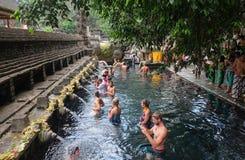 Bali Indonesien - September 9,2017: utlänningworshippers ber i vattnet på den Tirta Empul templet Tro det vatten från royaltyfri fotografi