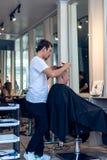 BALI INDONEZJA, CZERWIEC, - 2, 2017: Włosiany stylista przy fryzjera męskiego sklepem na Bali wyspie Fotografia Stock