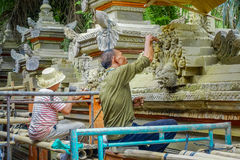 BALI INDONEZJA, KWIECIEŃ, - 05, 2017: Niezidentyfikowana para używa ścinaka robić sztuce cement, w Ubud Bali lokalizować wewnątrz Zdjęcia Royalty Free