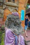 BALI INDONEZJA, KWIECIEŃ, - 05, 2017: Niezidentyfikowany mężczyzna odprowadzenie słucha piękna kamienna statua, wearnig purpurowa Zdjęcia Stock