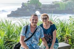BALI INDONEZJA, MAJ, - 4, 2017: Kobieta i jej syn na tle Pura Tanah udziału świątynia, Bali wyspa, Indonezja Zdjęcie Stock