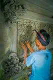 BALI INDONEZJA, MARZEC, - 08, 2017: Mężczyzna używa ścinaka robić sztuce na ścianie cement, w Denpasar Bali lokalizować wewnątrz Zdjęcia Royalty Free