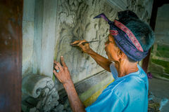 BALI INDONEZJA, MARZEC, - 08, 2017: Mężczyzna używa ścinaka robić sztuce na ścianie cement, w Denpasar Bali lokalizować wewnątrz Zdjęcie Royalty Free