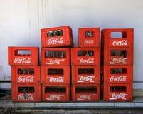Bali, Indonezja, Wrzesień/- 09, 2016: Brogować skrzynki butelki wśrodku koka-kola czerwonych plastikowych skrzynek przeciw białej Fotografia Stock