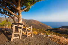 Bali, Island Crete, Greece, - June 25, 2016: Beautiful morning scenery with two wooden benches near the tree. Benches are installe Stock Photos