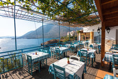 Bali, Island Crete, Greece, - June 23, 2016: The tables in the restaurant with view on the Mediterranean Sea and mountains. Restaurant with view on the sea and Stock Image