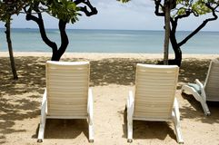 Bali Island - seats at beach. Indonesia, Bali Island, holiday resort in NusaDua. Beautiful beach with green palms and blue ocean water Stock Images