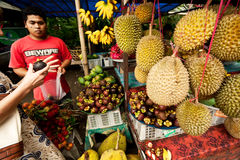 BALI - JANUARY 3: A man sells exotic fruits to local customers o Royalty Free Stock Photography