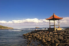 Bali ocean view. Traditional Balinese sala with red roof on a stone pier in Candidasa on Bali's Northeast coastline in Indonesia. Ocean view with blue sky and Royalty Free Stock Photo