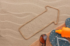 Bali pointer and beach accessories lying on the sand Royalty Free Stock Photo