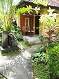 Bali resort patio garden. A photograph of the beautiful lush gardens of a tropical resort hotel in Bali, Indonesia.  Small lane leads to room patio with natural Royalty Free Stock Image
