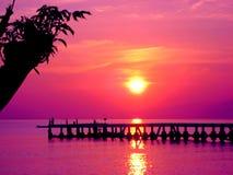 Bali sunrise over a jetty golden sunlight on the ocean Stock Photos