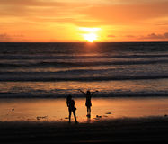Bali Sunset. Two girls pose for pictures on the beach in Bali, Indonesia Stock Photos