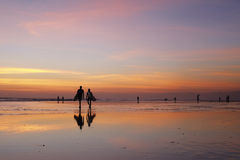 Bali Sunset Surfing. Kuta, Bali, Indonesia - August 10, 2013: Surfers returning to the beach after sunset Stock Photo