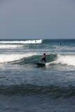 bali surfa Pojken gör att surfa på vågor Några surfare är nearb Arkivfoton