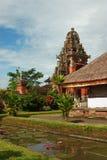 Bali tempel, med reflexion i vattnet och rosa liljor Royaltyfria Foton