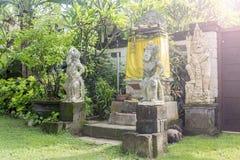 Bali tempel med tre statyer på frodig gräsplanträdgård arkivbilder