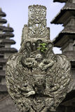 Bali temple detail. Hindu animist deity carving at Pura Tanan Ayun, an ancient Balinese temple in Indonesia, with typical Balinese Merus in the background Stock Photo