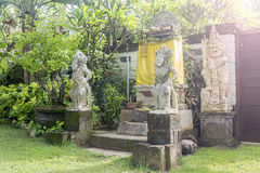Bali Temple with Three Statues On Lush Green Garden. This is a house temple or a small shirne where traditional daily offering are made. Guarded by guardian stock images