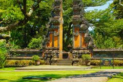Bali traditional gate with green grass and big tree tropical country style - photo indonesia royalty free stock images