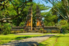Bali traditional gate with stone pathway and green grass - photo indonesia royalty free stock image