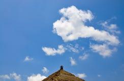 Bali tradizionale ha ricoperto di paglia il tetto contro un cielo blu con le nuvole Immagine Stock