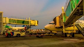 Balikpapan / Indonesia - 9/27/2018: The activity in the airport at dawn / dusk;. Boarding passengers, fueling, ground maintenance royalty free stock photography