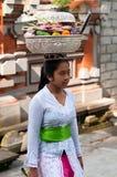 Balinees het Dragen van de Vrouw Dienstenaanbod op Haar Hoofd Stock Foto's
