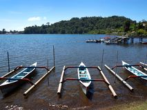Balinese boats, Lake Brataan scenic landmark. A photograph showing a few Balinese style fishing boats lined up against the shore of Lake Brataan, in the royalty free stock photography