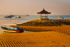 Balinese boats and pavilion in Sanur beach in the morning at dawn, Bali, Indonesia. Traditional Balinese ships Jukung in Sanur beach at sunrise, Bali, Indonesia royalty free stock photography