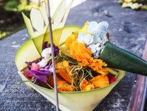 Balinese canang sari offering with orange flowers and incense. Balinese canang sari offering with orange flowers and an incense stick, Besakih temple, Bali Royalty Free Stock Photography