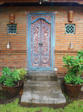 Balinese carved wood door. A photograph of a beautifully carved wooden door of a balinese house. Decorated with motifs of birds and flowers, and painted in red stock photo