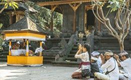 Balinese familie die in de Tempel van Goa bidden Lawah Stock Fotografie