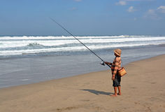 Balinese Fisherman Surf Casting on Legian Beach. Royalty Free Stock Images