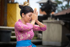 Balinese girl praying. She kneeling with joined hands in front of his head royalty free stock photo