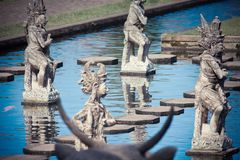 Balinese god at water background. Sculpture Balinese god at water background, Water Palace Bali Stock Photos